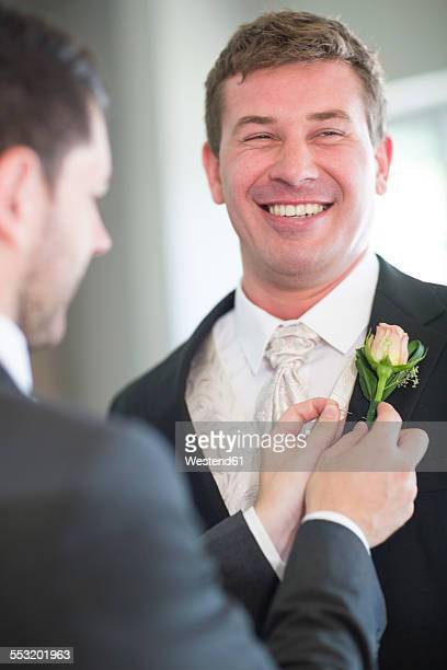 Groom getting ready for wedding with best man