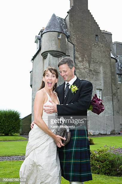 Groom grasping bride's breast, smiling, castle in background