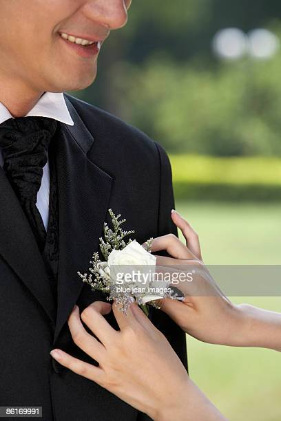 A groom has his corsage pinned