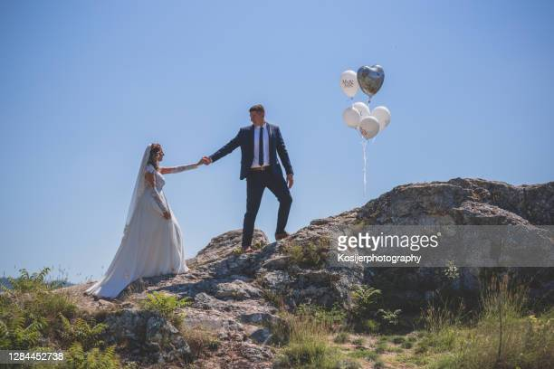 groom helping bride to climb the rocks - newlywed stock pictures, royalty-free photos & images