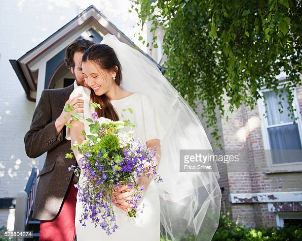 Groom hiding after bride in front of house
