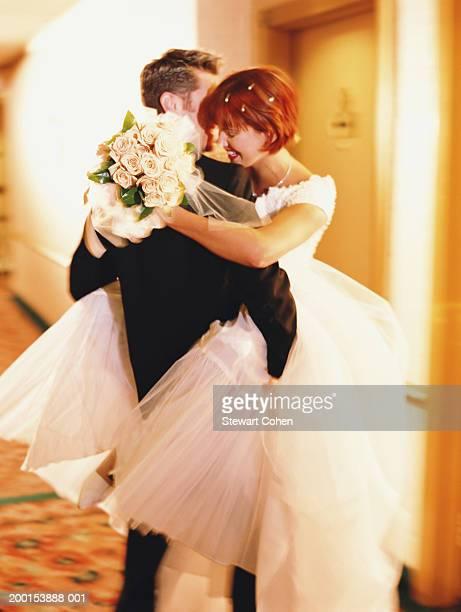 Groom holding bride in hallway outside hotel room