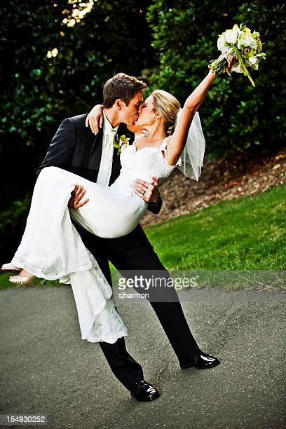 groom holding carrying and kissing bride with floral bouquet