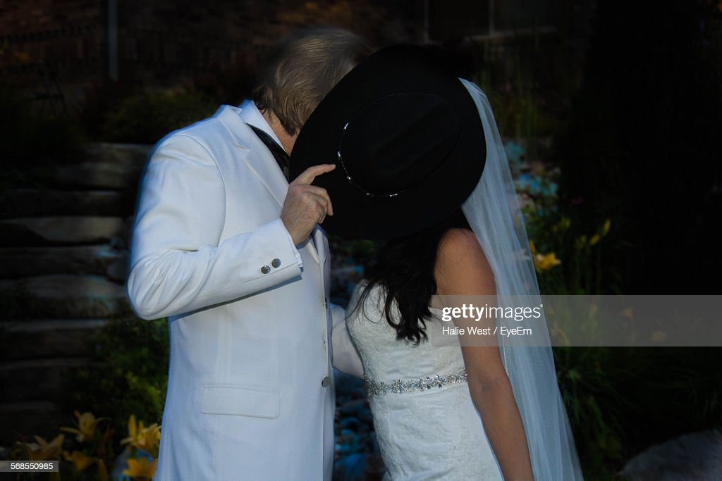 Groom Holding Hat While Kissing Bride : Stock Photo