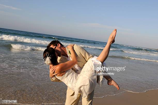 Groom holding his bride on beach