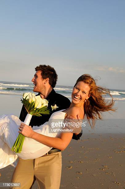 Groom holding his bride, smiling and happy