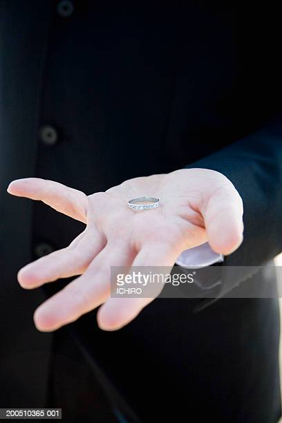 Groom holding wedding ring, close-up of hand
