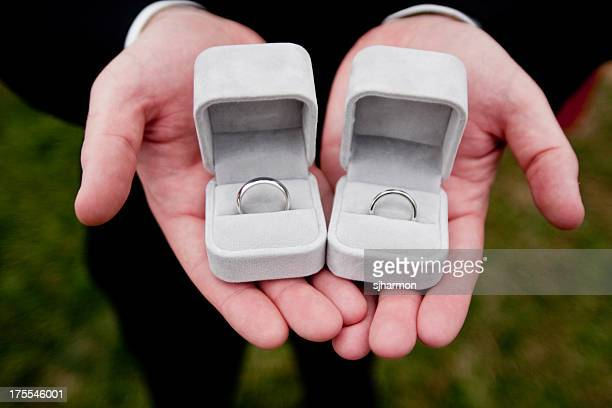groom holding wedding rings in outstretched hands jewlery boxes - skin diamond stock pictures, royalty-free photos & images
