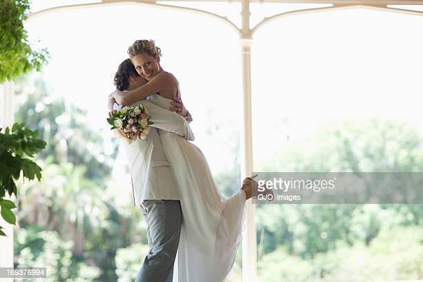 Groom hugging and lifting bride
