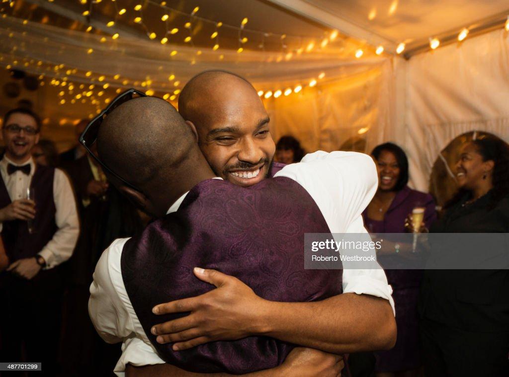 Groom hugging groomsman at reception : Stock Photo