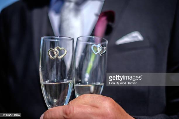 groom in a black suit holding two champagne glasses with heart symbols - finn bjurvoll stock-fotos und bilder