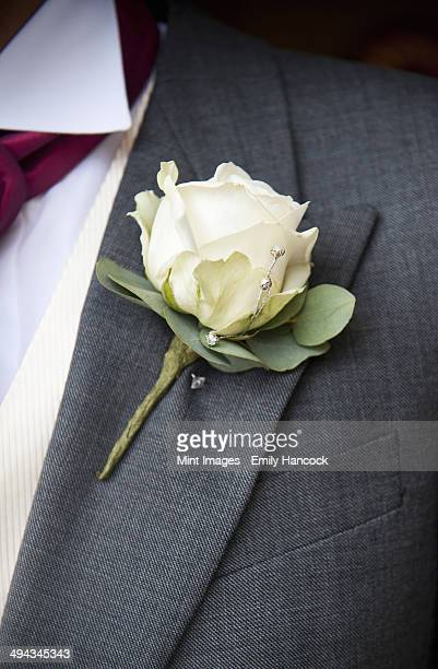A groom in a grey jacket and white shirt, with a white rose buttoniere, in his buttonhole.