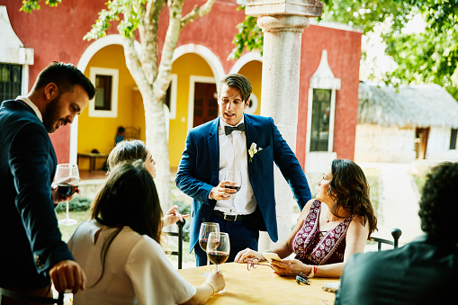 Groom in discussion with wedding guests during outdoor reception at tropical resort - gettyimageskorea