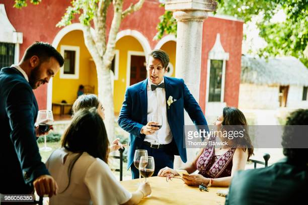 groom in discussion with wedding guests during outdoor reception at tropical resort - outdoor party imagens e fotografias de stock