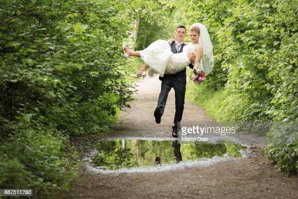 Groom is carrying his bride over a puddle
