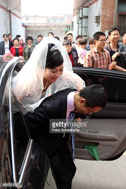 Groom is preparing to carry his bride from the car in which they arrived, into his parents house, while family, friends and neighbors look on.
