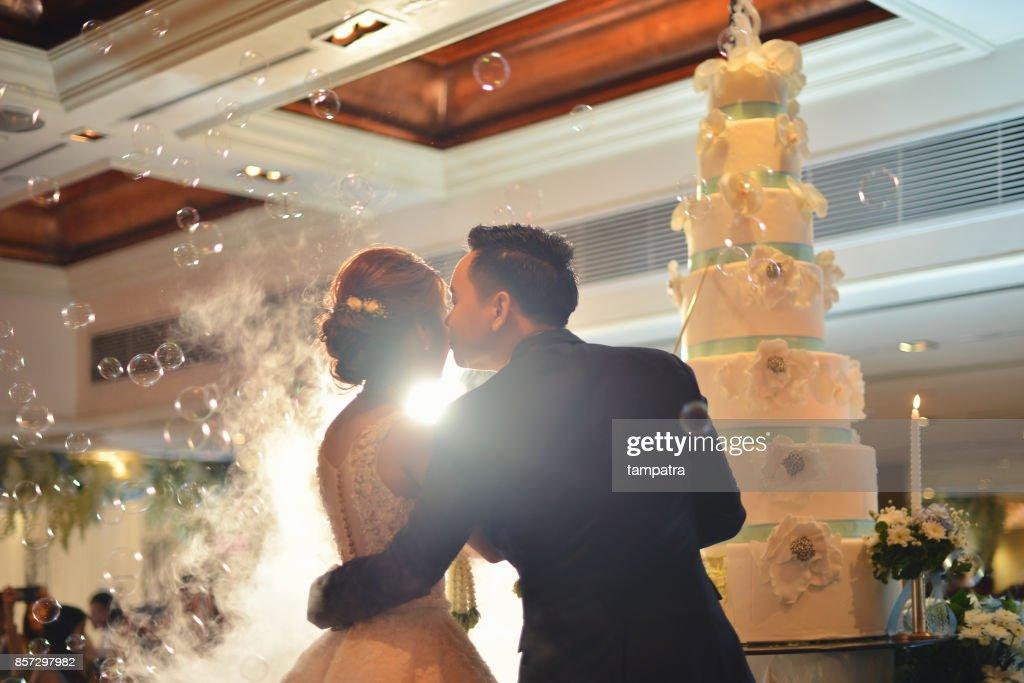 Groom kisses bride in front of cake in wedding ceremony in hall : Foto de stock