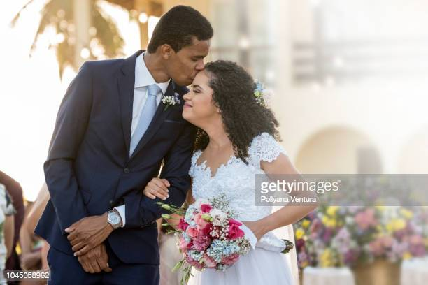 groom kisses his bride on the forehead - interracial wife photos stock photos and pictures