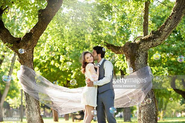 Groom kissing bride, bubbles mid-air, tulle, trees