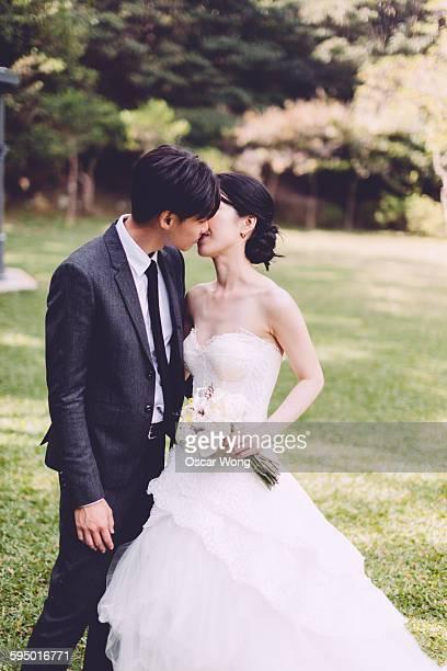 Groom kissing bride in park