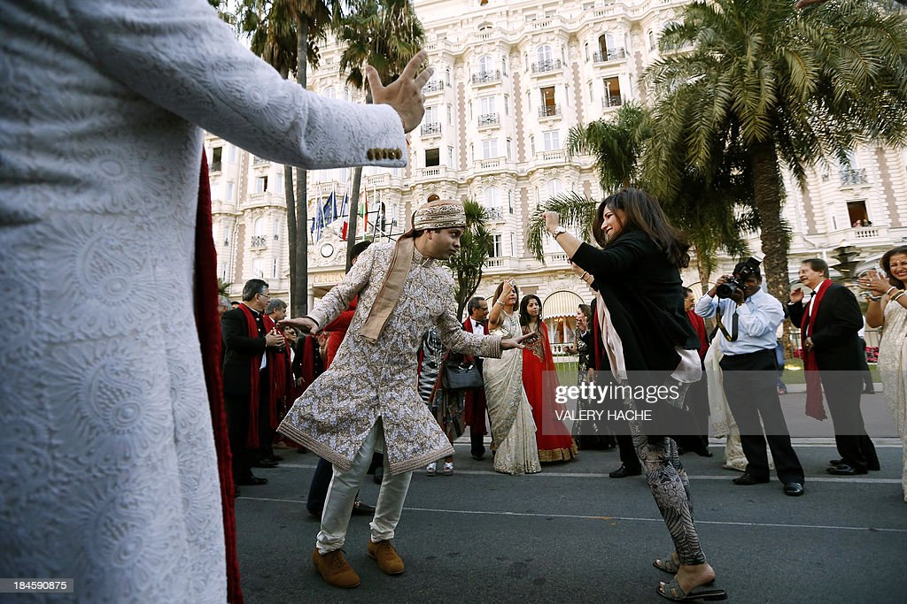 Groom Kunal Grover (L) dances with a guest in front of the Carlton Hotel in the southeastern French city of Cannes on October 14, 2013 during his wedding party. The Carlton palace was entirely booked for several nights to accomodate guests for the wedding of Grover and Ria Dubash.