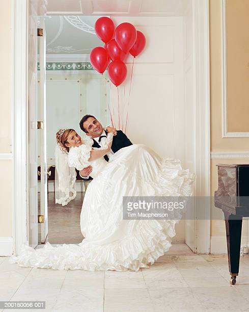 Groom lifting bride, smiling, portrait