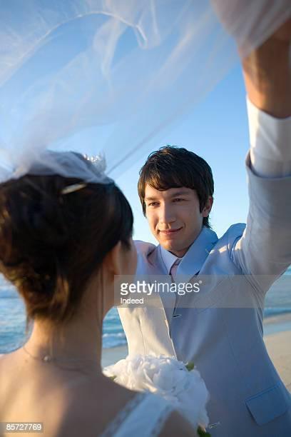Groom lifting bride's veil on beach, smiling