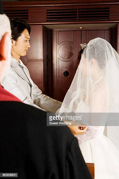 Groom lifting the bride's veil