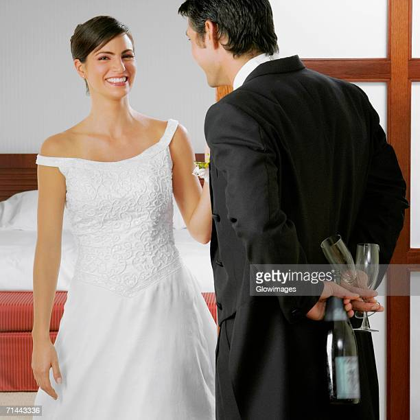 Groom looking at his bride and holding a bottle and glasses behind his back