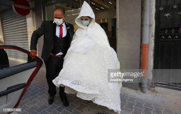 Groom Nisr Hadayed and bride Delye Hadayed wearing face masks as a measure against coronavirus as they prepare for their wedding ceremony in Khan...