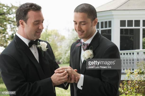 Groom placing ring on husband's finger