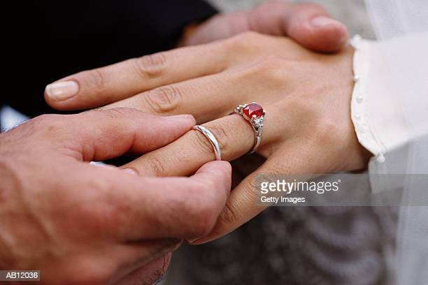 Groom placing wedding band on brides finger during ceremony, close-up