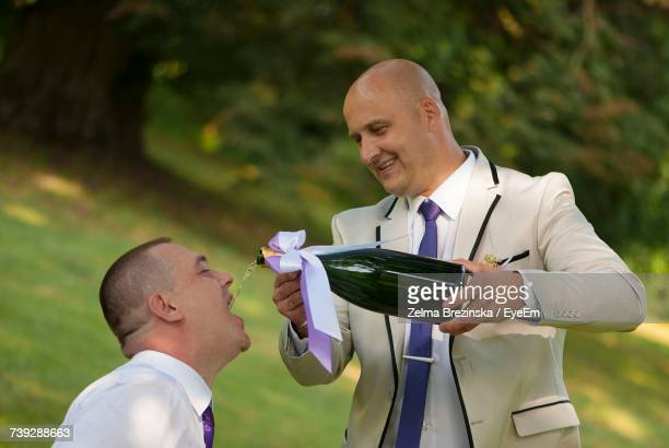 Groom Pouring Alcohol In Friend Mouth During Wedding Celebration