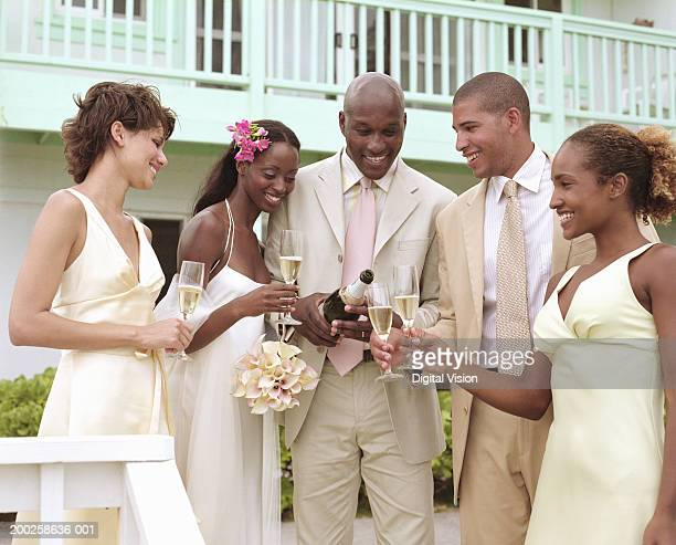 groom pouring champagne for bride, bridesmaids and best man, smiling - bridesmaid stock pictures, royalty-free photos & images
