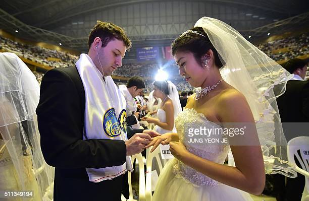 A groom puts a ring on the finger of his bride during a mass wedding held by the Unification Church at Cheongshim Peace World Center in Gapyeong east...