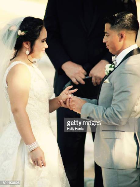 Groom putting ring on bride's finger at wedding ceremony