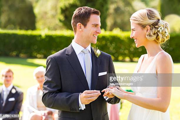 groom putting ring on bride's finger - wedding vows stock pictures, royalty-free photos & images