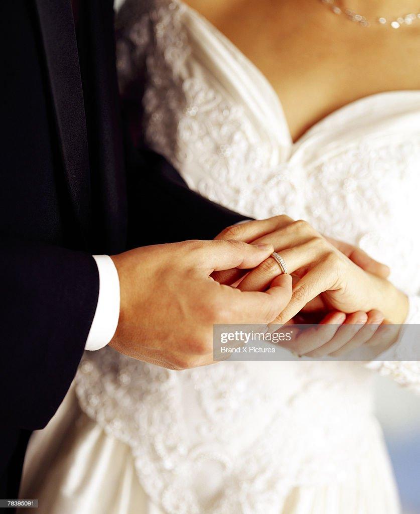 Groom putting ring on bride's finger : Stock Photo