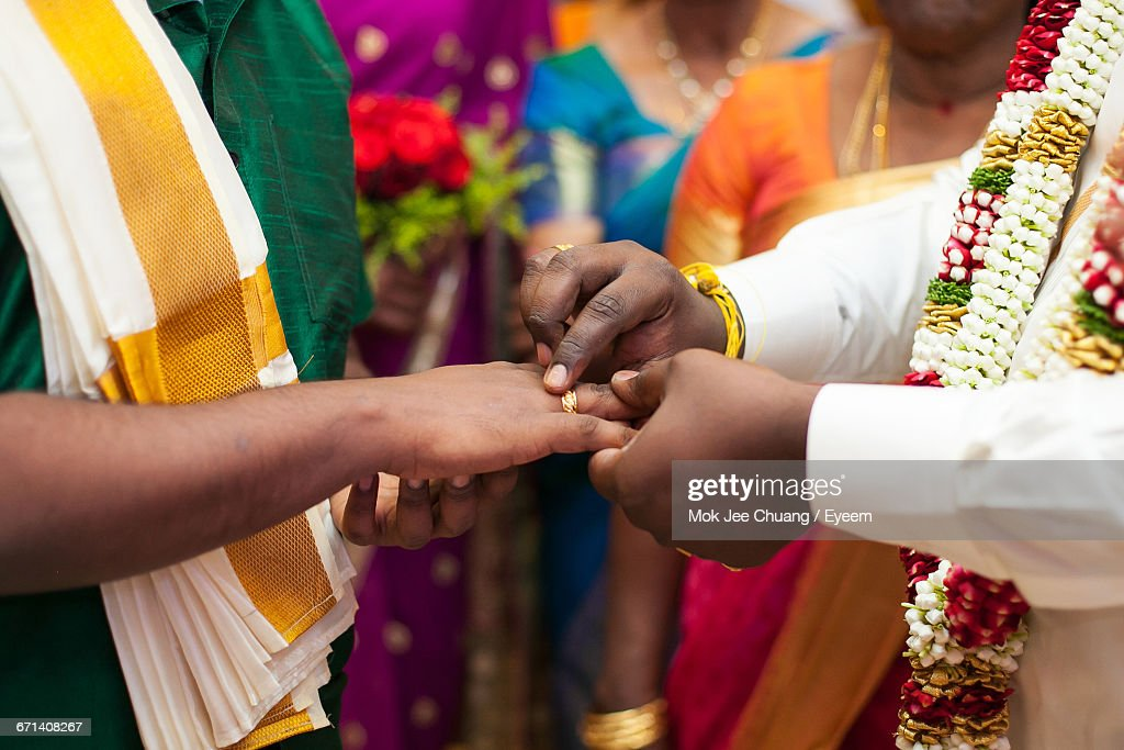 Groom Putting Ring Onto Brides Finger In Traditional South Indian