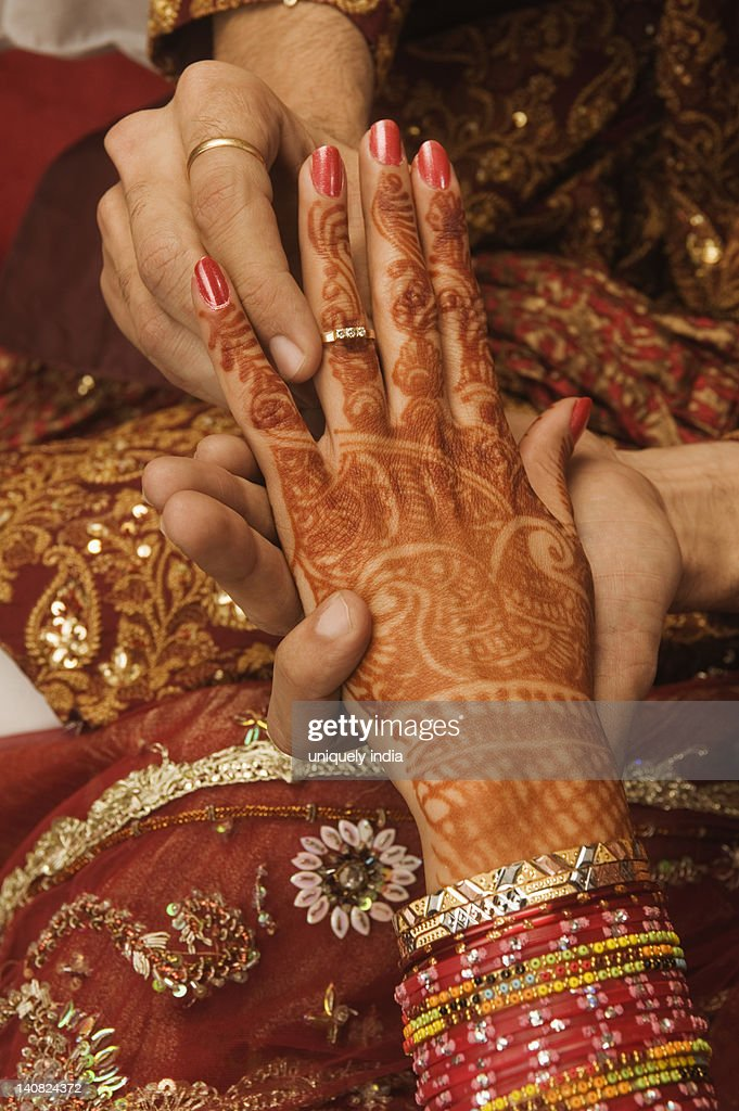Groom putting wedding ring on a bride's finger : Stock Photo