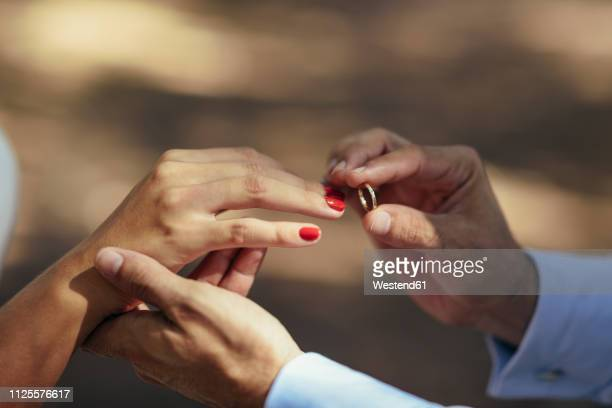 groom putting wedding ring on finger of bride, close up - matrimonio foto e immagini stock