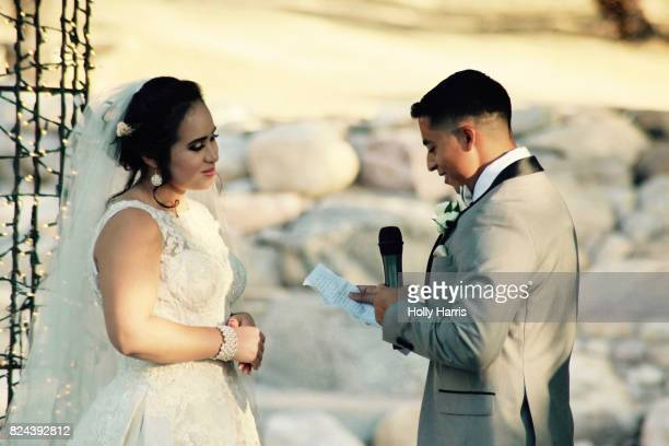 groom reading vows to bride at wedding ceremony - wedding vows stock pictures, royalty-free photos & images