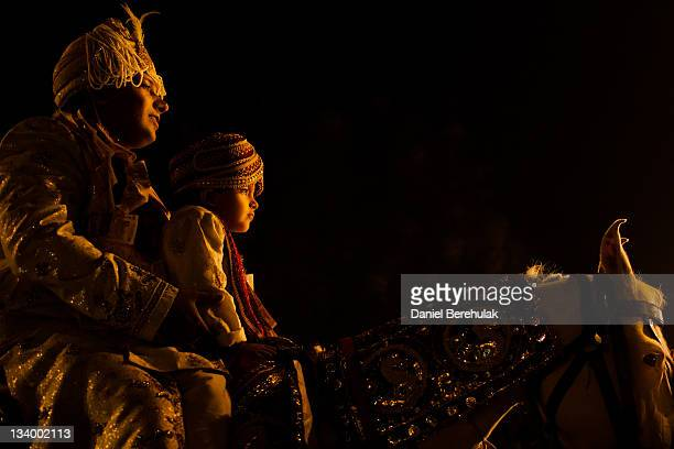 A groom rides on a white horse accompanied by a boy dressed in ornamental garment during his wedding procession on November 23 2011 in New Delhi...
