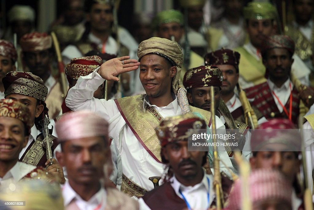 A groom salutes as he and others, employees of the Sanaa Municipality, wear traditional costumes and carry swords during a mass wedding ceremony on June 14, 2014, in the capital Sanaa. The ceremony was organized by the municipality for 350 members of its staff.