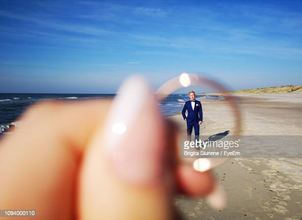 groom seen through wedding ring being held by bride at beach - wedding ring stock pictures, royalty-free photos & images