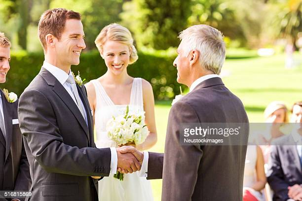 Groom Shaking Hands With Father In Garden