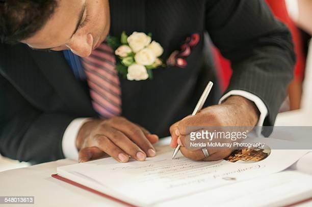 Groom signing marriage certificate