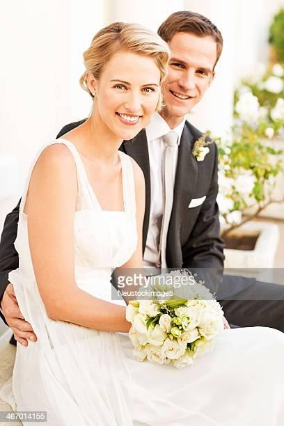 Groom Sitting With Arm Around Bride