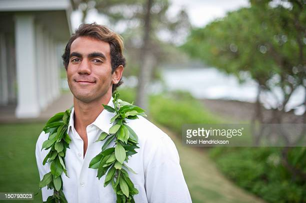 a groom smiles on his wedding day at the beach - lei day hawaii stock pictures, royalty-free photos & images