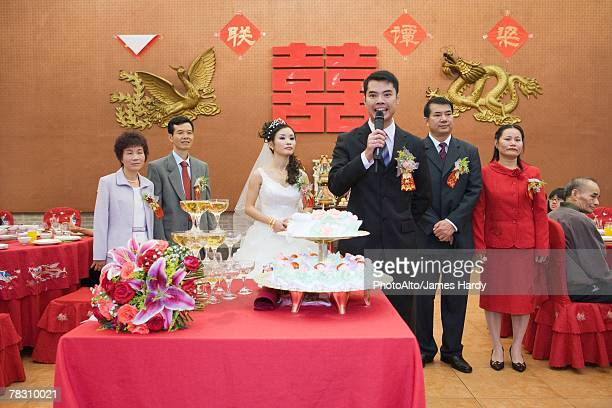 Groom standing in front of bride and parents, speaking into microphone